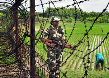 Indian female border guards keeps vigil as a farmer works in his field in Sonamura border in Tripura-Bangladesh border.